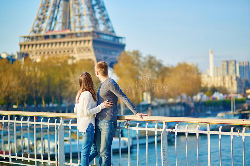 Young loving couple in Paris. Holding hands near the Eiffel tower royalty free stock images