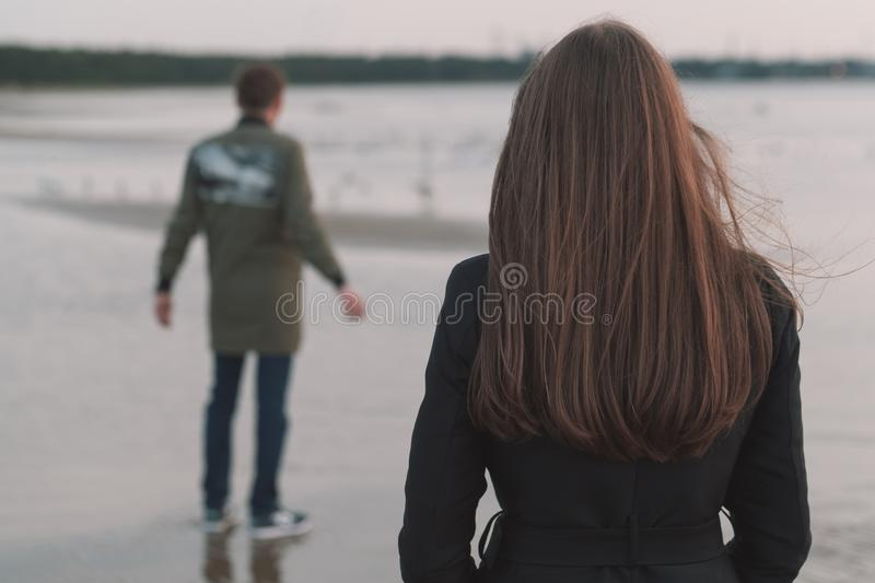 Young loving couple on the seashore in autumn. back view. Young loving couple on the seashore in autumn. back view royalty free stock photos