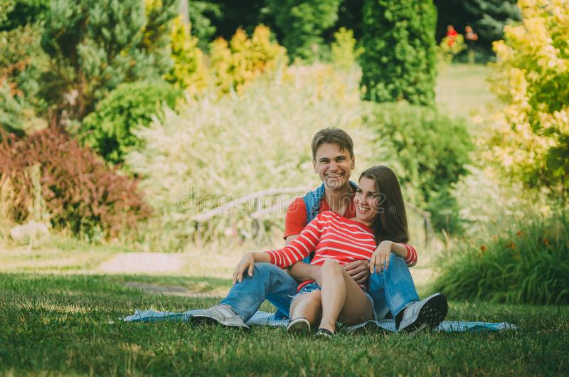 Young loving couple is sitting on a plaid in the park, hugging, fooling around and enjoying nature. Picnic for couples in love stock photography