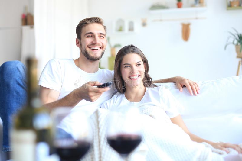 Young loving couple on sofa at home watching tv and laughing, drinking a glass of red wine. Young loving couple on sofa at home watching tv and laughing stock images