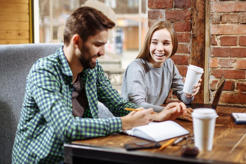 Young loving couple, students, sitting in a cafe while learning together and preparing for the seminar. royalty free stock images