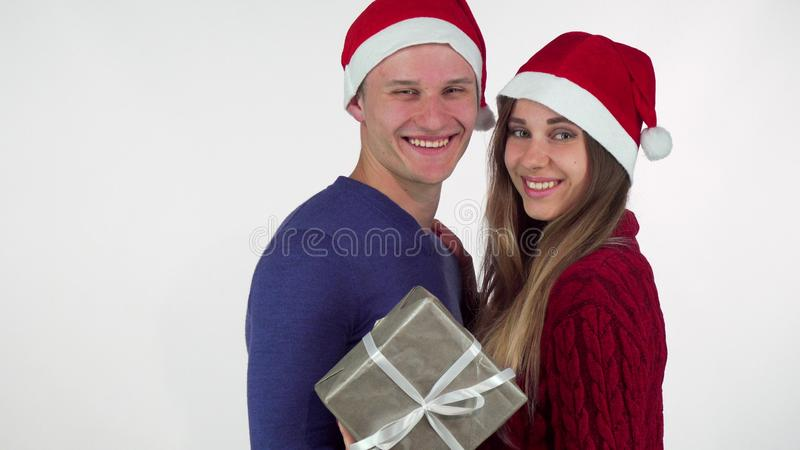 Young loving couple wearing Christmas hats smiling to the camera, holding a gift. Copy space on the side. Beautiful women and her boyfriend posing with a stock photos