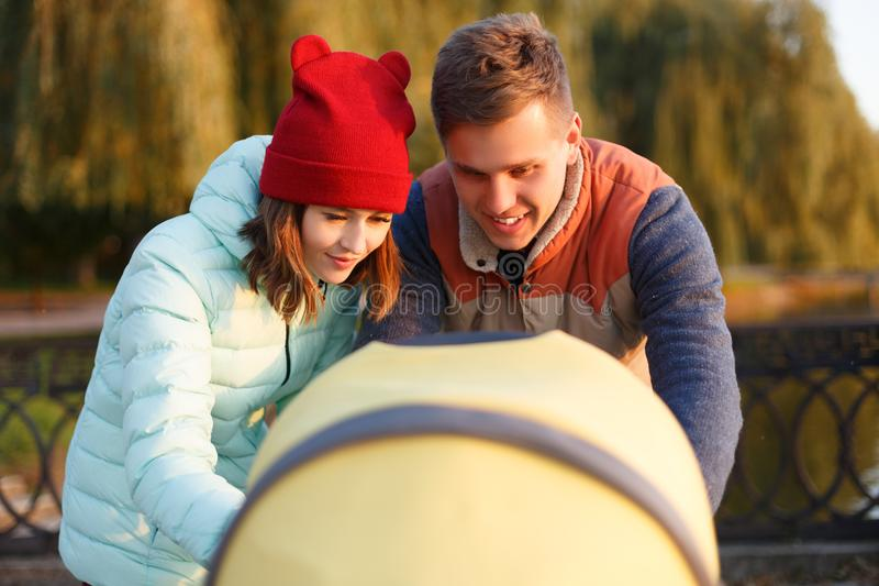 A young loving family walks by the lake with a stroller. Smiling parents couple with baby pram in autumn park look into cariage. L stock images