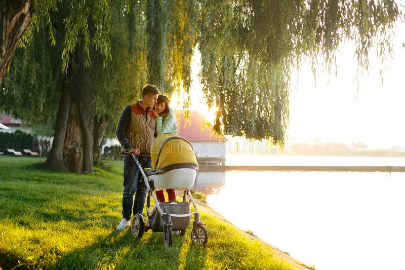 A young loving family walks by the lake with a stroller. Smiling parents couple with baby pram in autumn park. Love, parenthood, f stock image