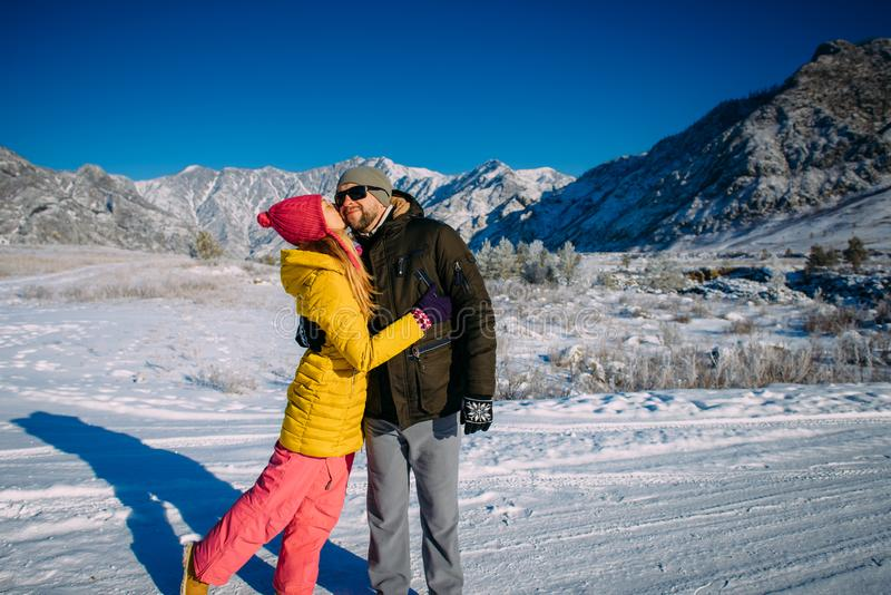 Young loving happy couple embraces and enjoys a new year vacation in the mountains. Guy and girl holding hands on the background royalty free stock photo