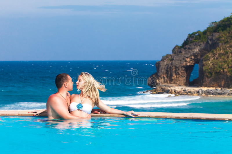 Young loving happy couple in the pool. Tropical sea in the back stock photo