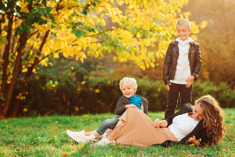 Young loving mother with her two sons spending free time outdoors. Family, autumn fashion and lifestyle stock photos