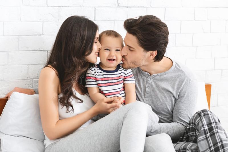 Young loving parents kissing their adorable baby son royalty free stock photo