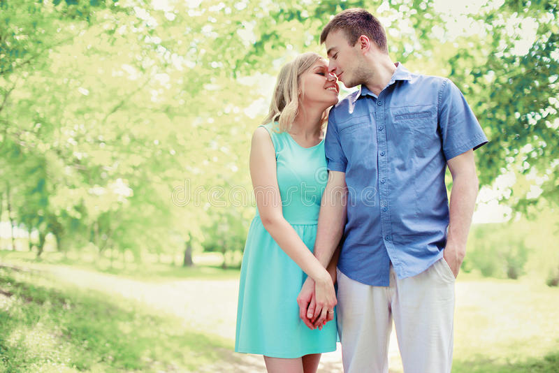 Young loving smiling couple walking together. In summer park stock photo