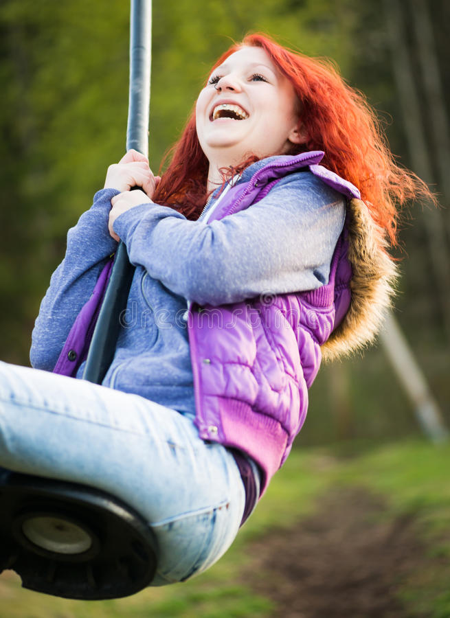 Young lucky girl is laughing while swinging royalty free stock photos