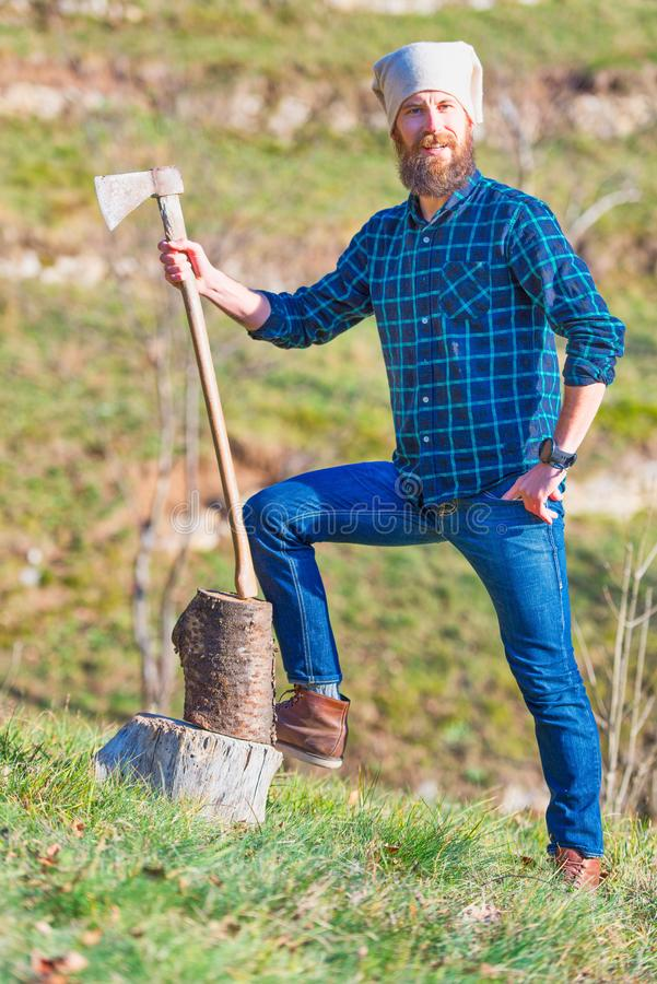 Young lumberjack with beard holds his ax in his hand.  royalty free stock images