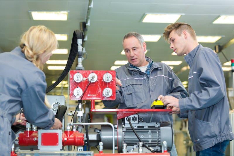 Young machine operator inspecting machine. Young machine operator inspecting the machine stock photo