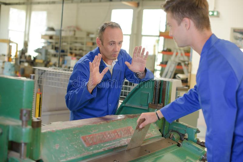 Young machine operator with manager. A young machine operator with manager stock images