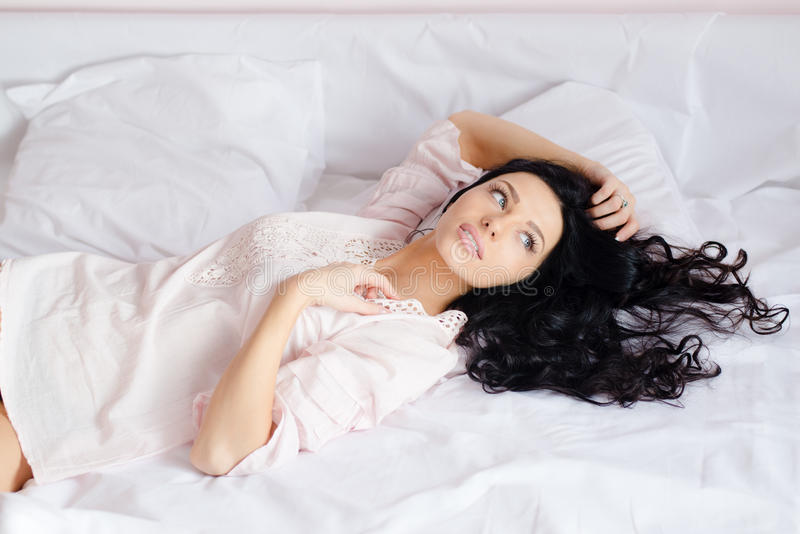 Young magic beautiful charming woman in white shirt lying on the bed & looking in window on white background closeup portrait stock photography