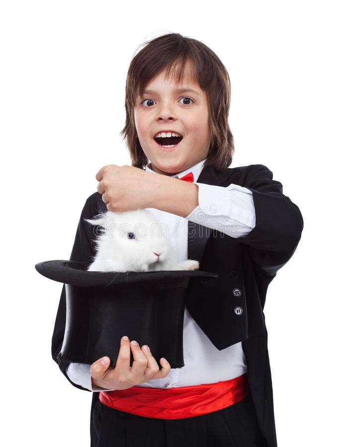 Young magician boy taking a rabbit out of his hat stock image