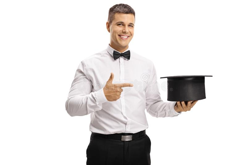 Young magician holding an empty hat and pointing stock image