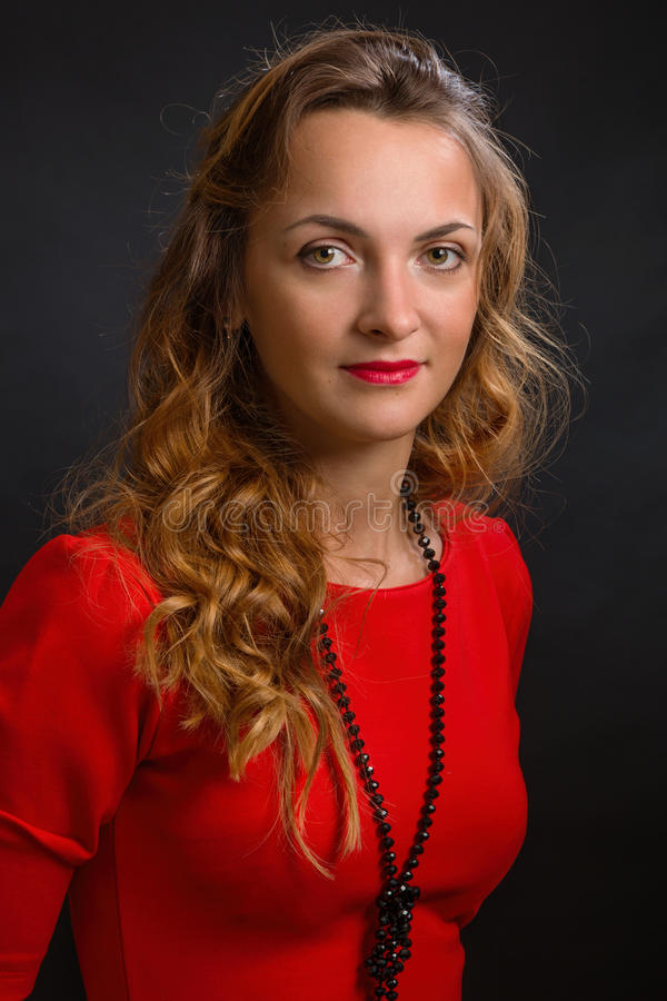 The young magnificent woman in an elegant dress of scarlet color with beautiful ringlets and a beads royalty free stock photo