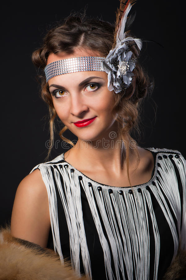 The young magnificent woman with scarlet lips in a skin from red fox and feather in hairstyle in Chicago style. The young magnificent woman with bright scarlet stock photo