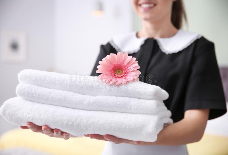 Young maid holding stack of towels and flower. In hotel room stock photo