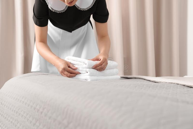 Young maid putting stack of fresh towels on bed in hotel room royalty free stock image