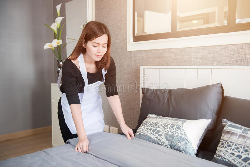 Young Maid Tidying Up Bed In Hotel Room, Cleaning Service Concept ...