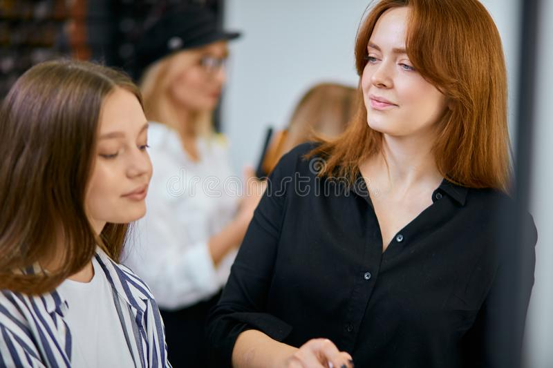 Young make-up artist doing makeup to young caucasian female stock image