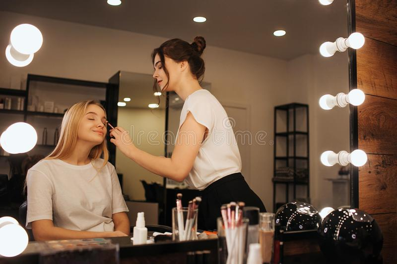 Young make up artist put make up of young woman`s face. She put eyeshadows using brush. Young blonde model sit calm in. Chair in beauty room royalty free stock photography