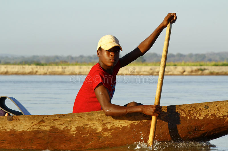 Young Malagasy african boy rowing traditional canoe on river royalty free stock photos