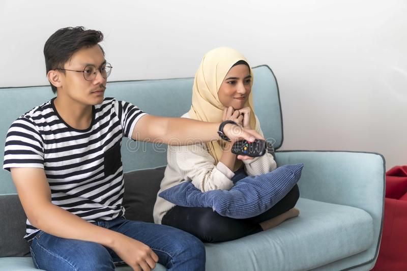 Young Malay Couple at the Sofa watching tv together. Holding remote, people, couch, adult, television, woman, leisure, home, entertainment, sitting, indoors royalty free stock photo