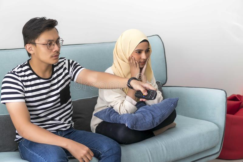 Young Malay Couple at the Sofa watching tv together. People, couch, adult, television, woman, leisure, home, entertainment, sitting, indoors, lifestyle, room stock photography