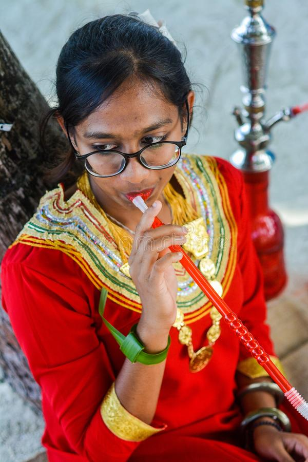 Young maldivian girl in national clothes smoking shisha. In Maldives stock images