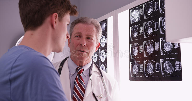 Young male adult caucasian reviewing brain xrays with mid aged p royalty free stock photography