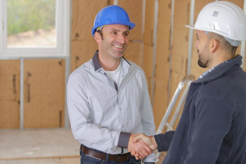 Young male architect and construction worker shaking hands royalty free stock photos