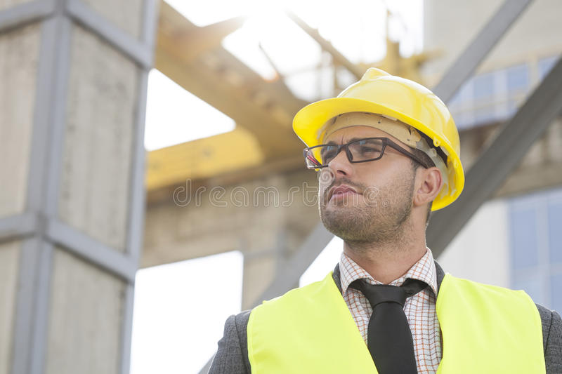 Young male architect wearing hard hat looking away at construction site stock photography