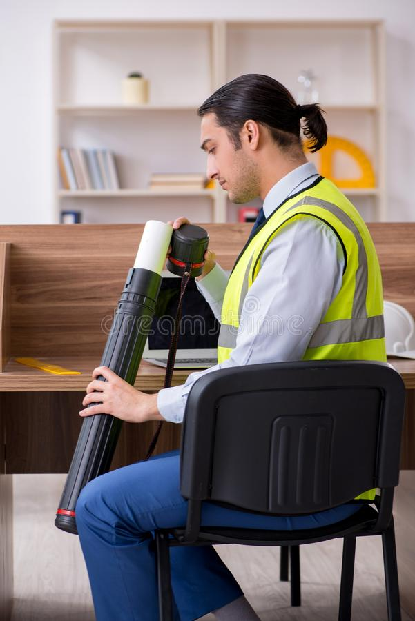 Young male architect working in the office. The young male architect working in the office stock image