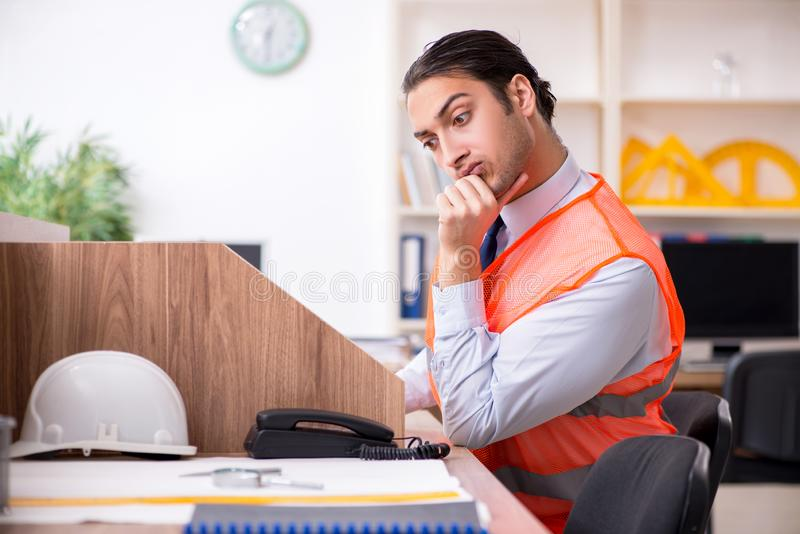 Young male architect working in the office. The young male architect working in the office stock photo