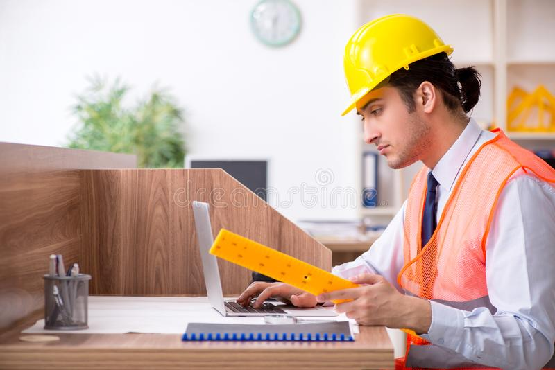 Young male architect working in the office. The young male architect working in the office stock images