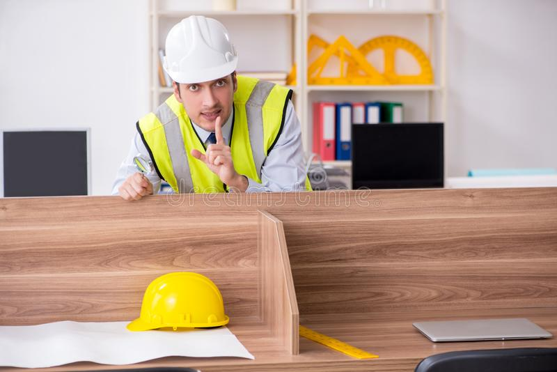 Young male architect working in the office. The young male architect working in the office royalty free stock image