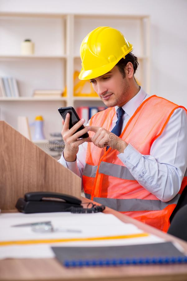 Young male architect working in the office. The young male architect working in the office royalty free stock photo