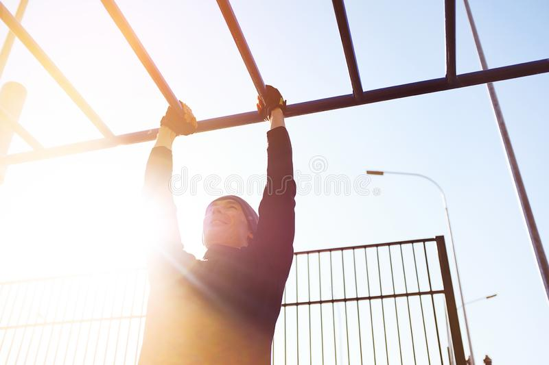A young male athlete does pull-UPS exercises on a horizontal bar, on a sports ground, outdoors, at dawn or on a Sunny day. The stock images