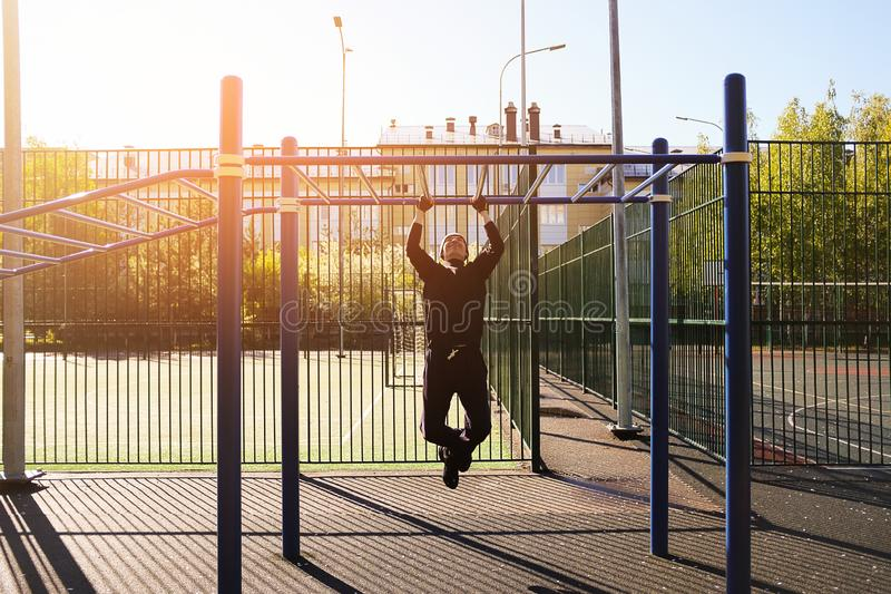 A young male athlete does pull-UPS exercises on a horizontal bar, on a sports ground, outdoors, at dawn or on a Sunny day. The royalty free stock images