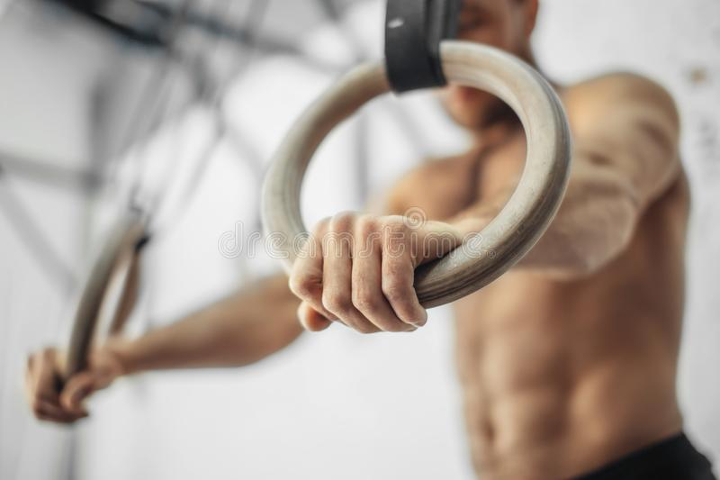 Male Athlete With Gymnastic Rings In The Gym. focus on rings. Young Male Athlete With Gymnastic Rings In The Gym. focus on rings royalty free stock images