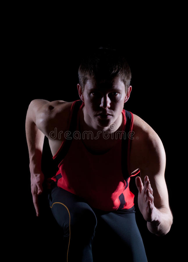 Young male athlete running. On black background royalty free stock images