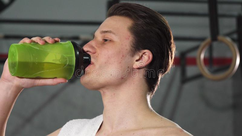 Young male athlete smiling joyfully drinking water stock photos
