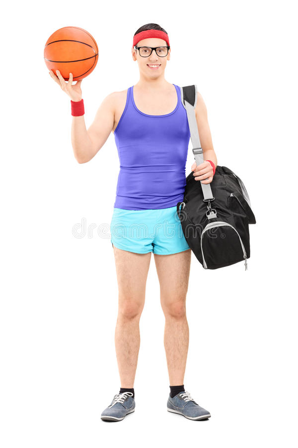 Young male athlete with sports bag holding a basketball stock photo