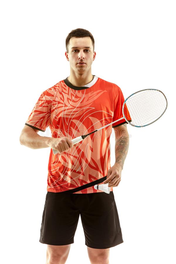 Young male badminton player over white background. Young man badminton player standing over white studio background. Fit male athlete stock photo