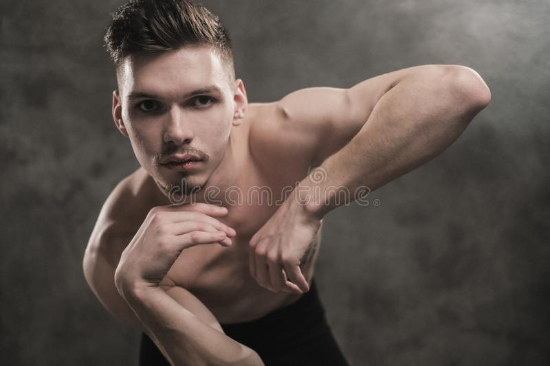 A young male ballet dancer with black leggings and a naked torso performs dance moves against a gray grunge background royalty free stock photos