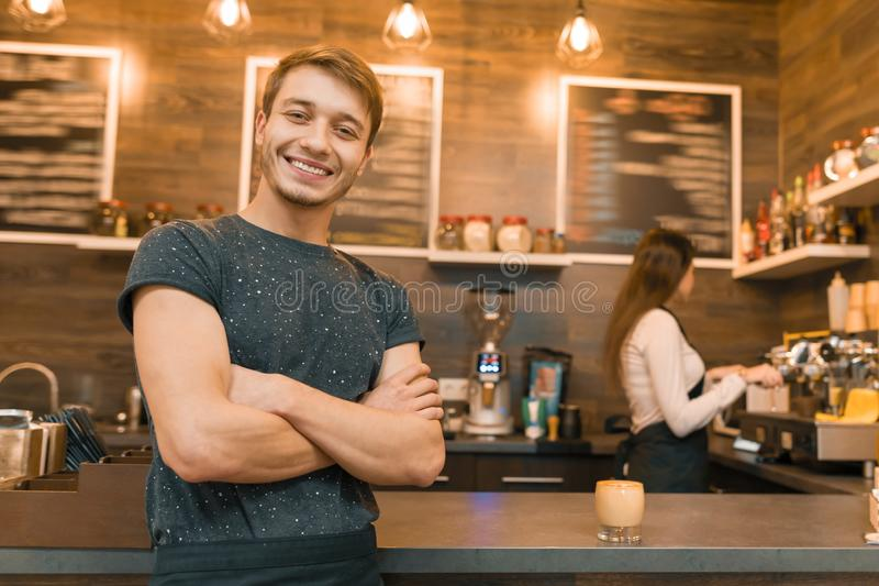 Young male barista coffee shop worker smiling looking at the camera with arms folded crossed near bar counter stock photos