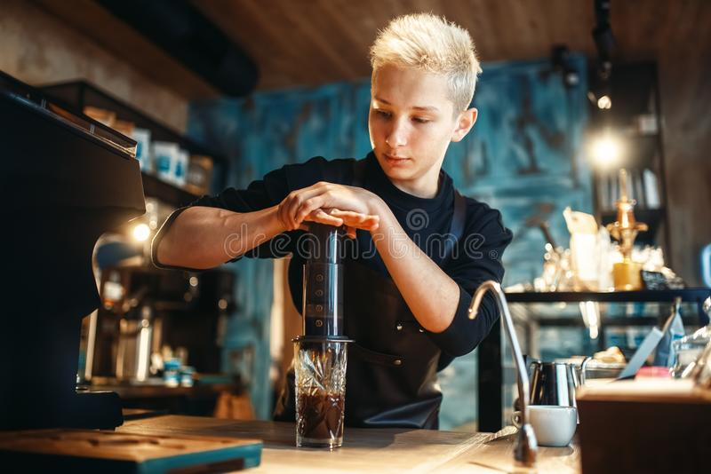 Young male barista makes fresh espresso in cafe royalty free stock photos