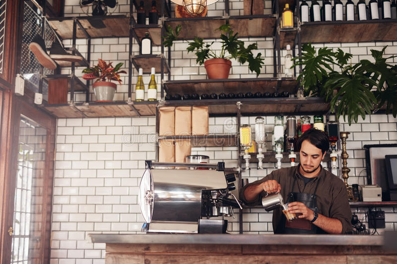 Young male barista making a cup of coffee royalty free stock image